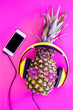 Pineapple in sunglasses and headphones is music fan. Pink background top view