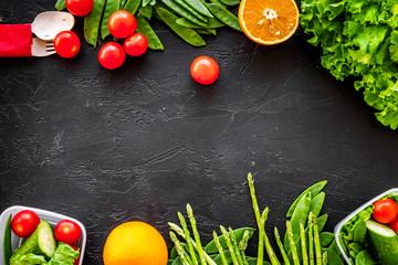 Vegearian lunch. Vegetables tomato, cucumber, asparagus, salad, orange on black background top view copyspace