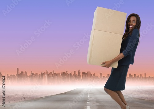 Businesswoman carrying boxes on road to city