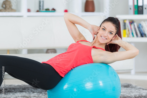 sporty woman doing pilates exercise with fit ball at home