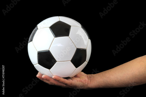 In de dag Bol Soccer ball on a hand and black background