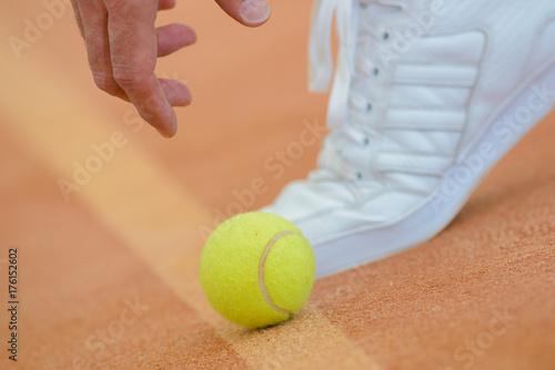 Staande foto Bol Closeup of hand reaching for tennis ball by foot