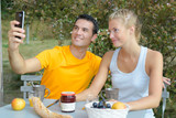 Couple taking selfie while eating breakfast outdoors - 176155497