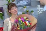 Florist passing bouquet of flowers to client