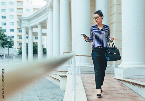 Fototapeta Business professional using smart phone in the city