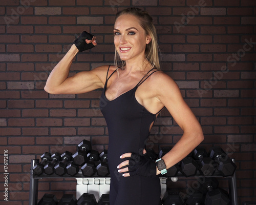 Woman bodybuilder showing the biceps against brick wall in the gym