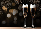 Two glasses with champagne on a table. New Year Celebration. - 176174035