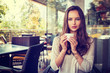 beautiful young girl sitting alone in a cafe drinks coffee