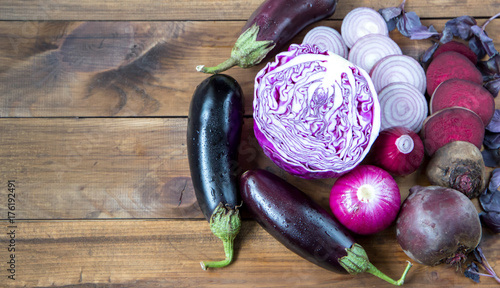 purple vegetables on wooden background - eggplant, beets, basil, onion, cabbage