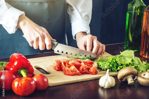 Fridge magnet The chef in black apron cuts vegetables. Concept of eco-friendly products for cooking