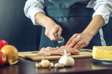 The chef in black apron cuts chicken fillet knife. Concept of eco-friendly products for cooking - 176195632