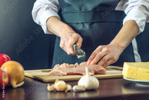 The chef in black apron cuts chicken fillet knife. Concept of eco-friendly products for cooking