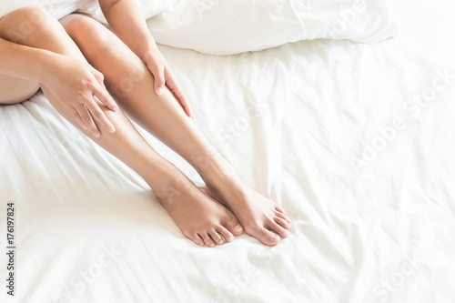 Closeup woman legs on white bed, beauty and skin care concept, selective focus - 176197824
