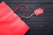Shopping bag and red sale tag with inscription Sale on black wooden table