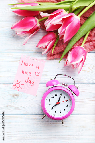 Bouquet of pink tulips with alarm clock and sheet of paper on wooden table