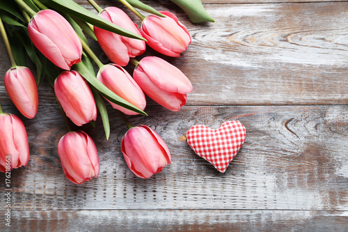 Pink tulips with red heart on grey wooden table
