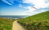 Hill pathway to the sea and parachuting man - 176224477