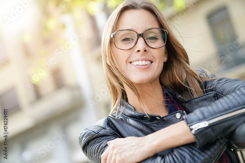 Portrait of cheerful girl in town with eyeglasses on
