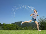 Girl running through arc of water