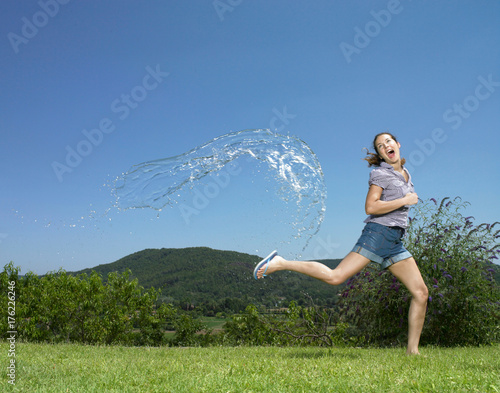 Girl running from arc of water