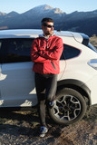 Athlete taking a break after outdoor workout on the mountain in late winter. Sporty man leaning on his car. - 176229444