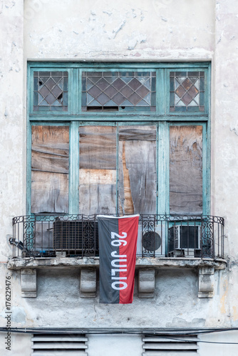 """Old windows setting with red and black flag """"26 Julio"""" in Cuba"""