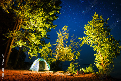 Tent set on the sandy beach among the trees on coast of a river with stars in the night sky