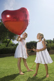 Young girls holding red heart balloon - 176237432