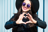 Happy young woman in glasses making a heart shape with her hands - 176247692