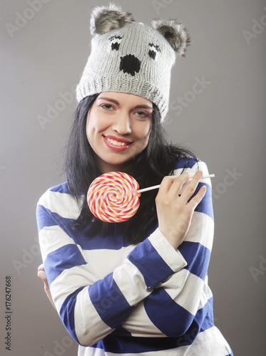woman wearing hat  looking into the camera and holding a lollipo Poster