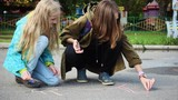 children drawing on an asphalt with the piece of chalk - 176250067
