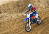The racer on a motorcycle participates in race motocrosses, goes on sand. Red blue suit. Close-up.
