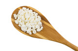 Bamboo spoon with grainy cottage cheese isolated on white background