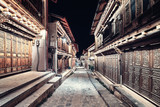 Vintage toned picture of illuminated empty street of Shangri La Old Town (Dukezong) at night, China.