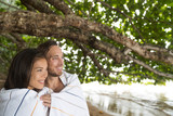 Couple at beach holiday hugging together under towels covering from rain - cute multiracial people lovers in love on travel vacation.