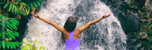Freedom zen happy girl with open arms meditating yoga at nature waterfall banner panoramic. Hawaii travel woman at Canyon Trail Waipoo Falls in Waimea, Kauai island, USA. - 176278046