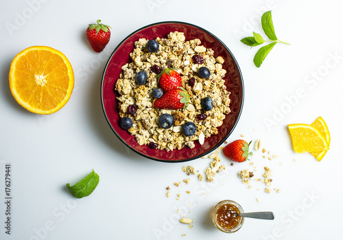 Granola with strawberries and blueberries on a white table © fluostudio