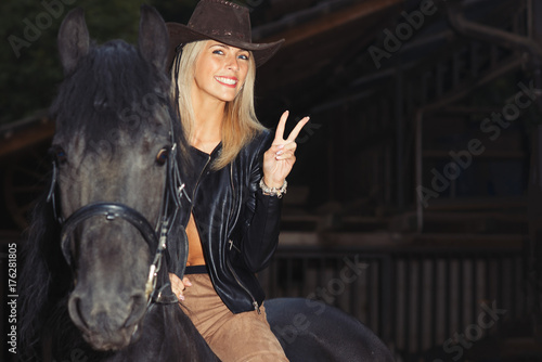 A beautiful blond girl over a black horse