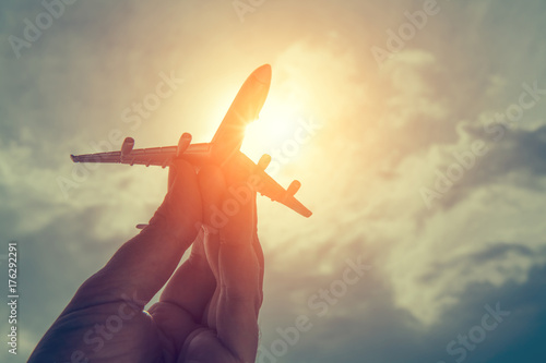 Fototapeta hand holding airplane model in front of cloudy sky background. air transportation concept.