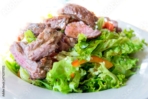 Veal steak salad with arugula, lettuce, halfs of small cherry tomatoes, stripes of sweet pepper and toasted bread - 176297052