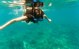 Woman diving or snorkelling in her summer vacation in clear tropical ocean water