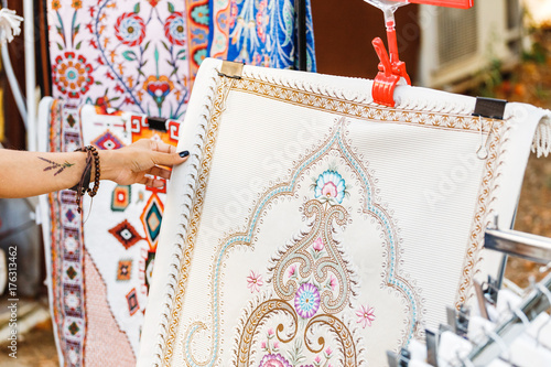 Woman chooses traditional muslim arabic carpet at turkish Grand Bazaar market Poster