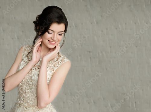 Half length portrait of brunette smiling woman dressed in sleeveless light evening dress.