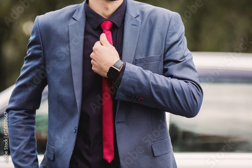 Successful businessman in a dark business suit with a red tie against the background of a car Poster