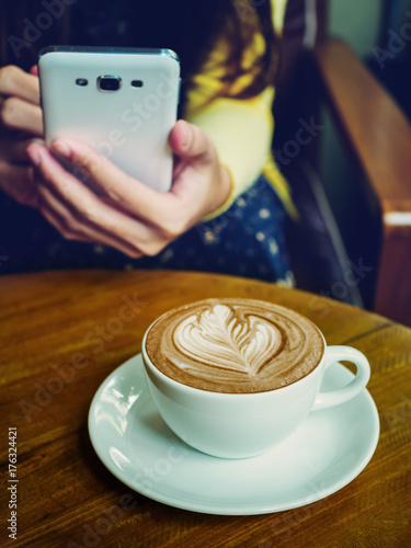 Papiers peints Cafe Latte coffee cup on wood table with woman holding smartphone in cafe.