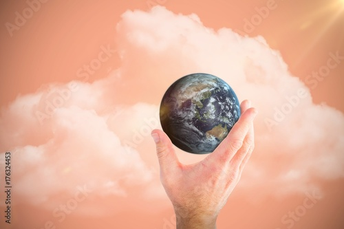 Composite image of hand presenting little earth