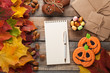 Blank white Notepad with pen on background of autumn leaves and candy on Halloween gummy candy, pumpkins and gingerbread cookies on old wooden background. Greeting card for Halloween
