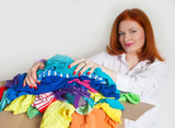 A woman is busy with the clutter in her wardrobe. - 176330222