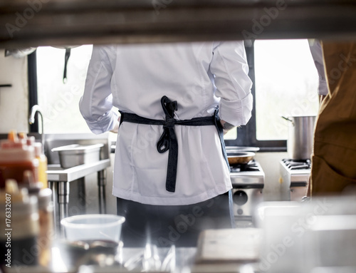 Rear view of chef cooking in the kitchen