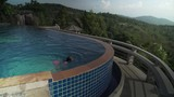 Young girl is swimming in pool atop a mountain stock footage video - 176332658